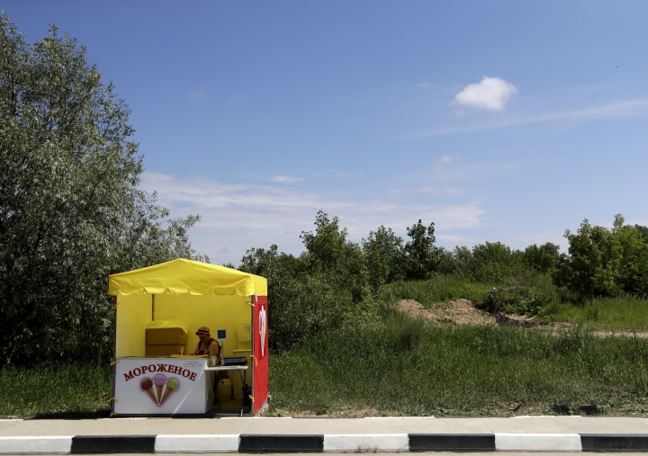 An ice cream seller waits for customers by the side of the road during the 2018 soccer World Cup at the in Nizhny Novgorod, Russia, Saturday, July 7, 2018. (AP Photo/Petr David Josek)