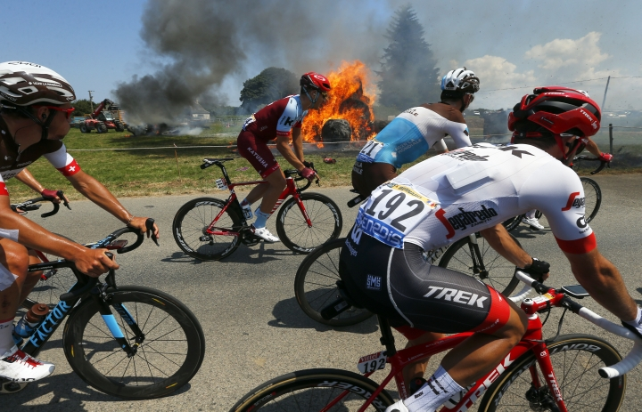 The pack rides past a burning haystack during the sixth stage of the Tour de France cycling race over 181 kilometers (112.5 miles) with start in Brest and finish in Mur-de-Bretagne Guerledan, France, Thursday, July 12, 2018. (AP Photo/Peter Dejong)