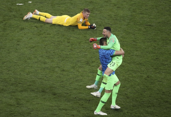 England goalkeeper Jordan Pickford lies down on the pitch as Croatia goalkeeper Danijel Subasic, right, celebrates at the end of the semifinal match between Croatia and England at the 2018 soccer World Cup in the Luzhniki Stadium in Moscow, Russia, Wednesday, July 11, 2018. (AP Photo/Thanassis Stavrakis)