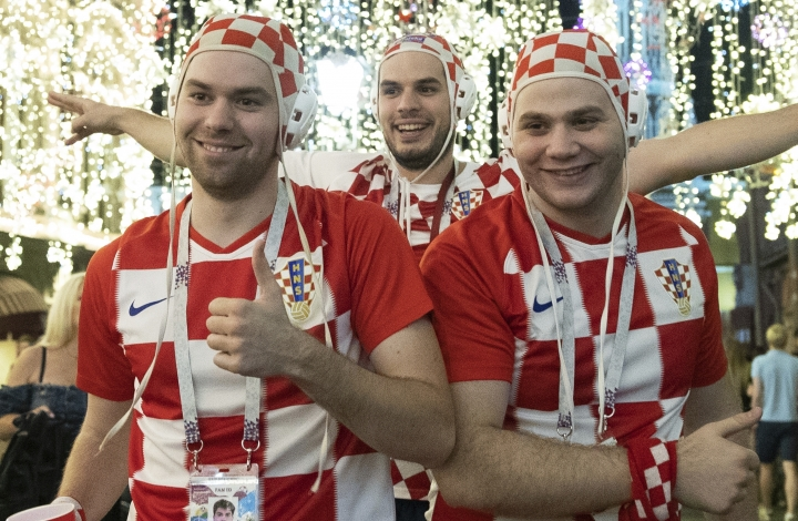 Croatia's soccer fans celebrate in Nikolskaya street near the Kremlin as their team won the semifinal soccer match between Croatia and England during the 2018 soccer World Cup at the Luzhniki stadium in Moscow, Russia, early Thursday, July 12, 2018. The St. Basil's Cathedral is left in the background. (AP Photo/Pavel Golovkin)