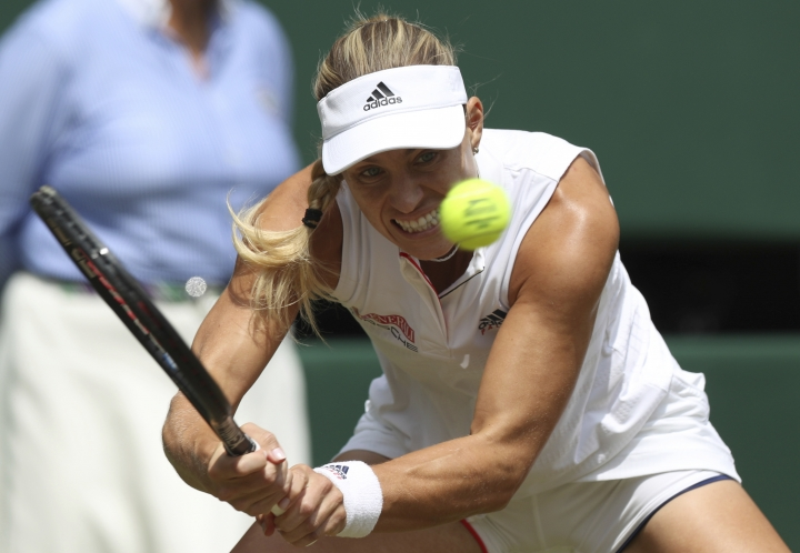 Angelique Kerber of Germany returns the ball to Jelena Ostapenko of Latvia during their women's semifinal match at the Wimbledon Tennis Championships in London, Thursday July 12, 2018. (Jonathan Brady/Pool via AP)