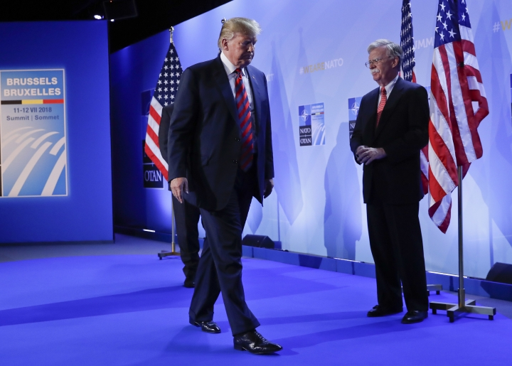 U.S. President Donald Trump walks off stage after holding a news conference before departing the NATO Summit in Brussels, Belgium, Thursday, July 12, 2018. On stage with Trump is National security adviser John Bolton, right. (AP Photo/Pablo Martinez Monsivais)