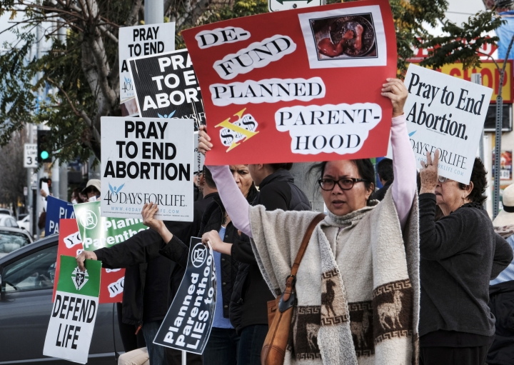 FILE - In this Feb. 11, 2017, file photo, protesters carry signs outside a Planned Parenthood health center in the Van Nuys section of Los Angeles. If a Supreme Court majority shaped by President Donald Trump overturns or weakens the right to abortion, the fight over its legalization could return to the states. (AP Photo/Richard Vogel, File)