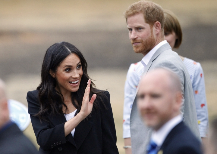 Prince Harry and Meghan Duchess of Sussex wave to members of the public at Trinity college, Dublin, Ireland, Wednesday, July 11, 2018. (AP Photo/Peter Morrison)
