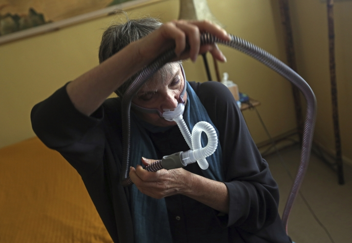 "Joelle Dobrow demonstrates how she puts on her sleep apnea breathing device at her home in Los Angeles Thursday, July 12, 2018. It's been two decades since doctors fully recognized that breathing that stops and starts during sleep is tied to a host of health issues, even early death, but there still isn't a treatment that most people find easy to use. Dobrow said it took her seven years to find one she liked. ""I went through 26 different mask styles,"" she said. ""I kept a spreadsheet so I wouldn't duplicate it."" (AP Photo/Reed Saxon)"