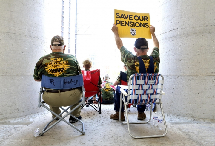 Roger Hulsey, left, 69, of Jasper, Ala., and Mike Barnett, right, 61, of Springville, Ala., both retired coal miners sit in the shade of the columns to protest at the Ohio Statehouse for protection of their pension rights Thursday, July 12, 2018, in Columbus, Ohio. The nation's burgeoning pension crisis has spurred thousands of workers and retirees to rally in Ohio's capital. Unionized coal and steel miners, teamsters, bakers, tobacco workers and others filled the lawn and steps of the Ohio Statehouse a day ahead of a congressional field hearing on the issue. (Eric Albrecht/The Columbus Dispatch via AP)