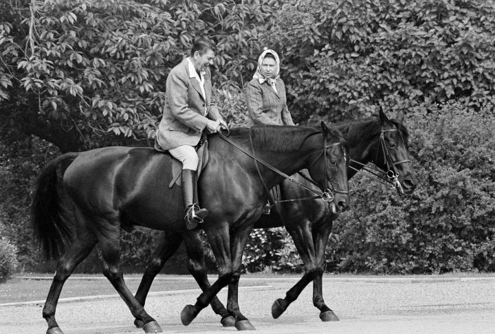 FILE - In this June 8, 1982 file photo, U.S. President Ronald Reagan, on Centennial, and Britain's Queen Elizabeth II, on Burmese, go horseback riding in the grounds of Windsor Castle, England. US President Trump enjoys flouting diplomatic rules and expressing himself in bold and sometimes mocking tweets and comments, but that side of his personality is unlikely to surface when he takes tea Friday, July 13, 2018 with Queen Elizabeth II. The president and his wife Melania are not expected to make waves during the visit with the 92-year-old monarch, who has met every U.S. president since Dwight Eisenhower with the exception of Lyndon Johnson, who never visited Britain while in office. (AP Photo/Bob Daugherty, File)