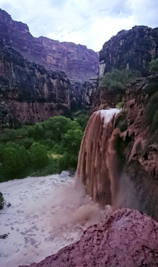This Wednesday, July 11, 2018 photo released by Benji Xie shows flooding from a waterfall on the Havasupai reservation in Supai, Ariz. About 200 tourists were being evacuated Thursday from a campground on tribal land near famous waterfalls deep in a gorge off the Grand Canyon. (Benji Xie via AP)
