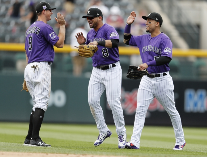 Colorado Rockies second baseman DJ LeMahieu, left fielder Gerardo Parra and right fielder Carlos Gonzalez, from left, celebrate the team's 5-1 win against the Arizona Diamondbacks in a baseball game Thursday, July 12, 2018, in Denver. (AP Photo/David Zalubowski)