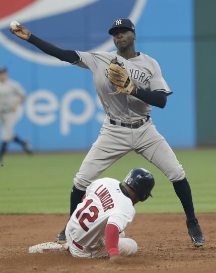 New York Yankees' Didi Gregorius throws to first base after getting Cleveland Indians' Francisco Lindor out at second base during the fifth inning of a baseball game, Thursday, July 12, 2018, in Cleveland. Michael Brantley was out at first base for the double play. (AP Photo/Tony Dejak)