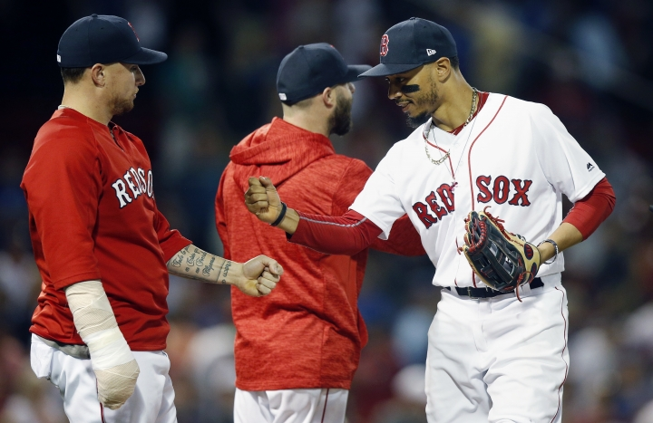 Boston Red Sox's Mookie Betts, right, celebrates with Christian Vazquez, left, after the Red Sox defeated the Toronto Blue Jays 6-4 during a baseball game in Boston, Thursday, July 12, 2018. (AP Photo/Michael Dwyer)