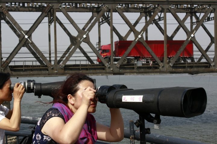 In this May 24, 2018, photo, tourists peek through the telescopes into North Korea as a truck crosses the friendship bridge connecting China and North Korea in the Chinese border town of Dandong, opposite side of the North Korean town of Sinuiju. China's imports from North Korea plunged 92.6 percent in June compared with a year earlier under U.N. sanctions imposed to stop Pyongyang's nuclear and missile programs, the customs agency said Friday, July 13, 2018. (Chinatopix Via AP)