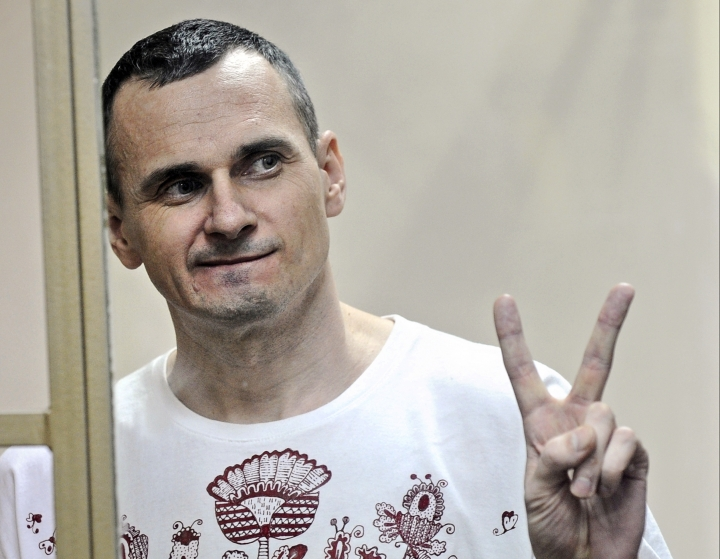 FILE - In this Tuesday, Aug. 25, 2015 file photo, Oleg Sentsov gestures as the verdict is delivered, as he stands behind bars at a court in Rostov-on-Don, Russia. The mother of a jailed Ukrainian filmmaker who has been refusing food for nearly two months is asking Russian President Vladimir Putin to pardon him it was reported on Friday, July 13, 2018. Oleg Sentsov, a vocal opponent of Russia's annexation of Crimea, was sentenced in 2015 to 20 years for conspiracy to commit terror acts. (AP Photo, file)