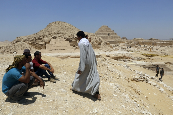 Excavation workers take a rest in front of Unas Pyramid, left, and the step pyramid of Saqqara, in Giza, Saturday, July 14, 2018. Archaeologists say they have discovered a mummification workshop dating back some 2,500 years at an ancient necropolis near Egypt's famed pyramids. (AP Photo/Amr Nabil)