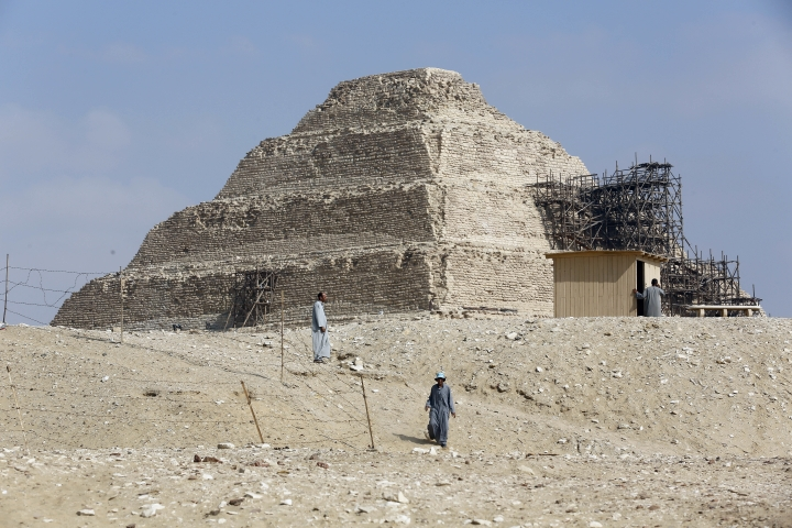 Excavation workers walk in front of the step pyramid of Saqqara, in Giza, Saturday, July 14, 2018. Archaeologists say they have discovered a mummification workshop dating back some 2,500 years at an ancient necropolis near Egypt's famed pyramids. (AP Photo/Amr Nabil)