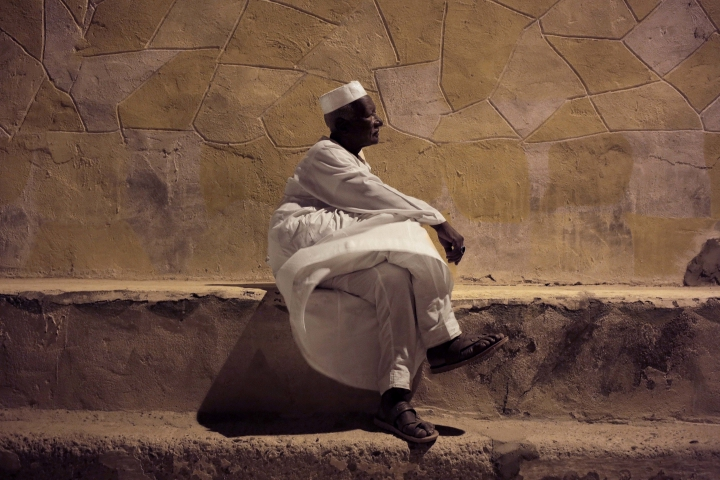 In this May 7, 2018, photo, 65-year old Mohammed Haroun sits in front of his home in Wadi Karkar, a new complex under construction in the desert west of Lake Nasser, Aswan, Egypt. Evicted from their ancestral lands to make way for the world's largest man-made lake behind the Aswan Dam, Egypt's Nubians have found both pain and nostalgia in memories of the peaceful and uncorrupted life they once had. (AP Photo/Nariman El-Mofty)