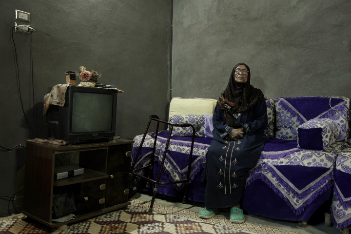 """In this May 9, 2018, photo, 85-year-old grandmother Naemah Hussein sits in her home """"tahgeer"""" Eneiba village, northern Aswan, Egypt. Speaking Arabic haltingly with a heavy Nubian accent, Hussein, said her house in her original home village of Eneiba was right on the banks of the Nile, where she baptized her first two children. Eneiba at the time had one of the best river ports in the country, built by the British in the 1930s. (AP Photo/Nariman El-Mofty)"""