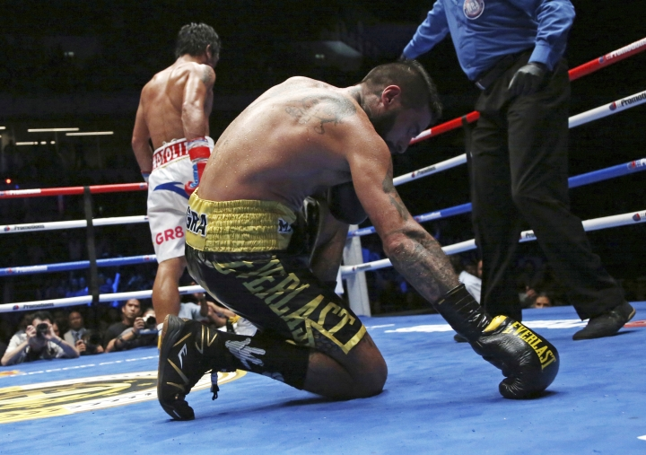 Lucas Matthysse of Argentina falls after receiving a punch by Manny Pacquiao of the Philippines during their WBA World welterweight title bout in Kuala Lumpur, Malaysia, Sunday, July 15, 2018. Pacquiao clinched his 60th victory with a seventh-round knockout of Matthysse, his first stoppage in nine years.(AP Photo/Yam G-Jun)