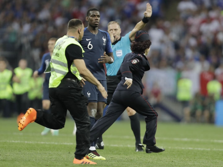 France's Paul Pogba watches a security staffer chasing a pitch invader during the final match between France and Croatia at the 2018 soccer World Cup in the Luzhniki Stadium in Moscow, Russia, Sunday, July 15, 2018. (AP Photo/Natacha Pisarenko)