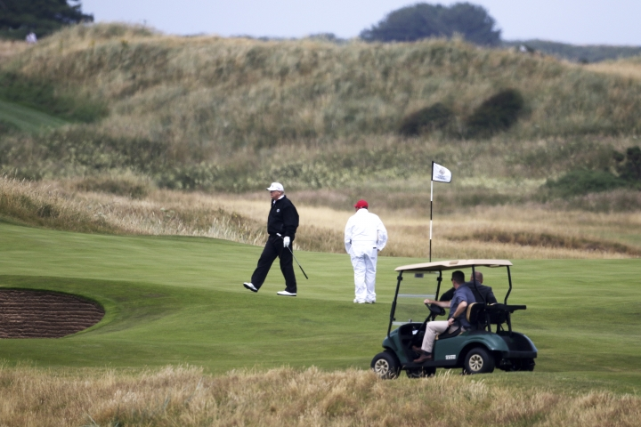 U.S. President Donald Trump walks off the 4th green while playing at Turnberry golf club, in Turnberry, Scotland, Saturday, July 14, 2018. A dozen demonstrators have staged a protest picnic on the beach in front of the Trump Turnberry golf resort in Scotland where President Donald Trump is spending the weekend with the first lady. (AP Photo/Peter Morrison)