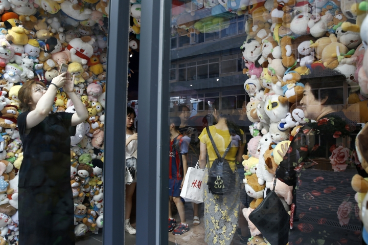 In this Sunday, July 15, 2018, photo, women take souvenir photos with soft toys on display at an arcade games shop in Beijing. China's economic growth slowed in the quarter ending in June, adding to challenges for Beijing amid a mounting tariff battle with Washington. (AP Photo/Andy Wong)