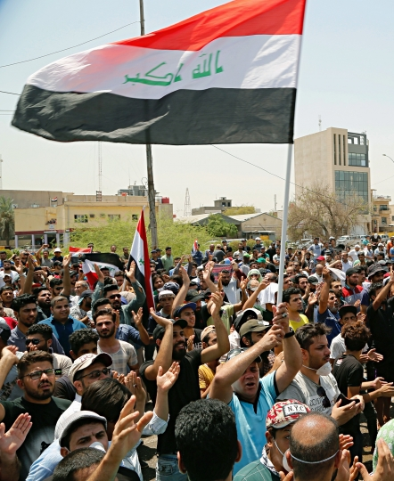 Iraqi protesters wave national flags in front of the provincial council building during a demonstration in Basra, 340 miles (550 km) southeast of Baghdad, Iraq, Sunday, July 15, 2018. Iraqis demanding better public services and jobs took to the streets again on Sunday in the southern oil-rich province of Basra, as authorities put security forces on high alert and blocked internet on the sixth day of protests in the country's Shiite heartland. (AP Photo)