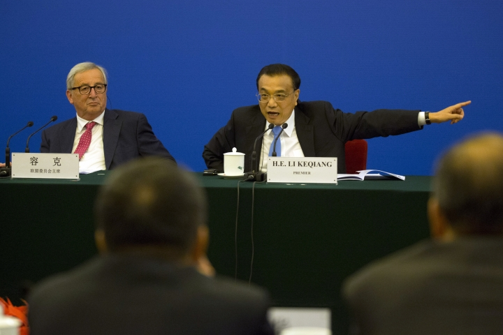 Chinese Premier Li Keqiang, gestures as he delegates a Chinese official to look into the problems brought up by European businessmen as European Commission President Jean-Claude Juncker, looks on during the China-EU Business Roundtable held at the Great Hall of the People in Beijing, China, Monday, July 16, 2018. (AP Photo/Ng Han Guan, Pool)