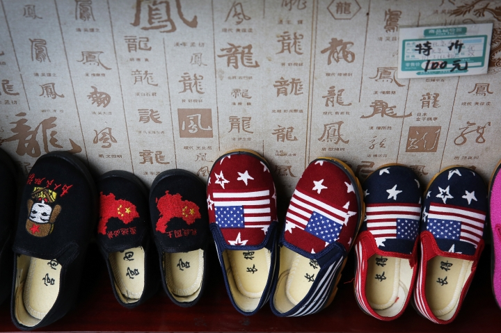 In this July 13, 2018, photo, Chinese made children shoes carrying a Chinese map and U.S. flags are on display for a sale at a shop in Beijing. China announced it filled a World Trade Organization challenge Monday, July 16, 2018, to U.S. President Donald Trump's proposal for a tariff hike on $200 billion of Chinese goods, reacting swiftly amid deepening concern about the economic impact of their spiraling technology dispute. (AP Photo/Andy Wong)