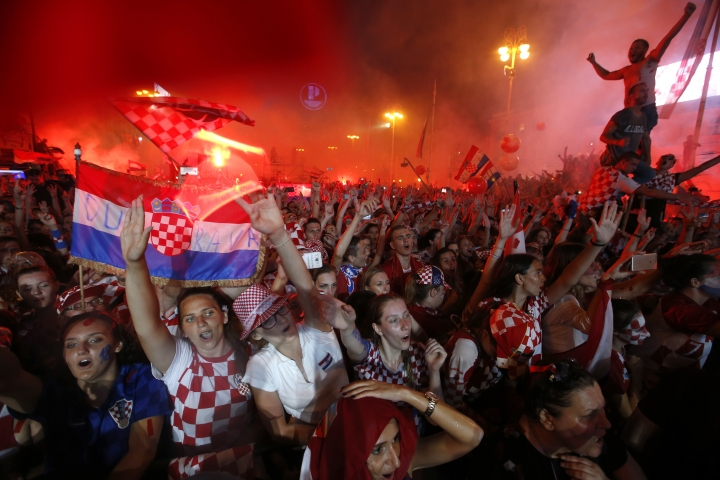 Croatia national soccer team members are welcomed with their national flags waved upon arrival in Zagreb, Croatia, Monday, July 16, 2018. Euphoria gave way to a mixture of disappointment and pride for Croatia fans after their national team lost to France in its first ever World Cup final. (AP Photo/Darko Vojinovic)