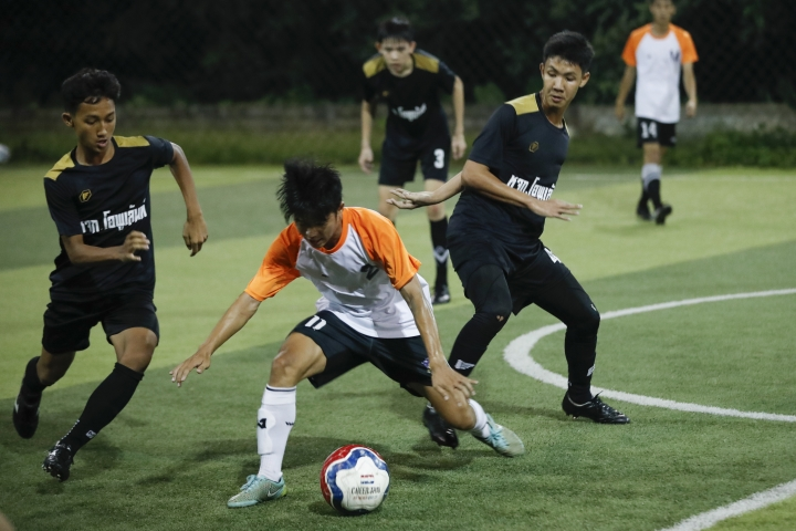 In this July 15, 2018, photo, Wild Boars football team, in black, play a local team during a Mae Sai football league soccer match in Mae Sai district in Chiang Rai province, northern Thailand. At least 3 of the 12 boys and coach of another local team who were rescued from a cave in northern Thailand last week are stateless, living in a limbo that puts serious restrictions not only on their upward mobility, but even on their right to travel outside of Chiang Rai, the northern province where they live. (AP Photo/Vincent Thian)