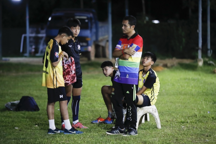 In this July 15, 2018, photo, the coach of one of Thailand's Wild Boars soccer teams, Nopparat Kanthawong, right, talks with his team in Mae Sai district in Chiang Rai province, northern Thailand. At least 3 of the 12 boys and coach of another local team who were rescued from a cave in northern Thailand last week are stateless, living in a limbo that puts serious restrictions not only on their upward mobility, but even on their right to travel outside of Chiang Rai, the northern province where they live. (AP Photo/Vincent Thian)