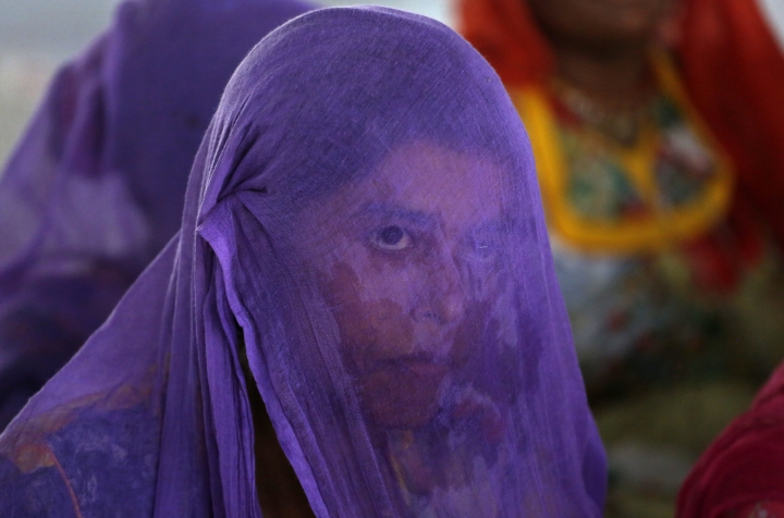 FILE- In this July 5, 2018 file photo, an Indian woman, who wears a veil as part of tradition, attends a meeting to condemn recent incidents of mob attacks, in Ahmadabad, India. India's highest court on Tuesday asked the federal government to consider enacting a law to deal with an increase in mob violence and lynchings that have mostly followed rumors that the victims either belonged to members of child kidnapping gangs or were beef eaters and cow slaughterers. (AP Photo/Ajit Solanki, File)