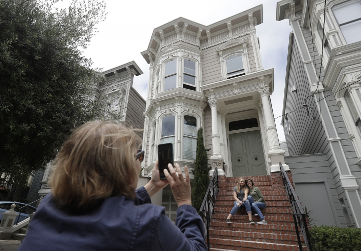 """Aries Layton, seated left, and her aunt Kelsy Layton pose as Debra Layton, Aries' grandmother and Kelsy's mother, foreground, takes photos outside a Victorian home made famous by the television show """"Full House"""" in San Francisco, Tuesday, July 17, 2018. Tour buses will no longer be swinging by the San Francisco house made famous in the popular 1990s sitcom """"Full House."""" The San Francisco Municipal Transportation Agency voted Tuesday to ban commercial vehicles from Broderick Street after neighbors complained. (AP Photo/Jeff Chiu)"""
