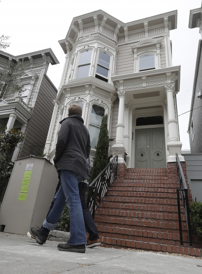 "Pedestrians walk outside a Victorian home made famous in the popular television 1990s sitcom ""Full House"" in San Francisco, Tuesday, July 17, 2018. The exterior of the Broderick Street house was used as the family's residence in the original show and in a Netflix reboot in 2016. The San Francisco Municipal Transportation Agency voted Tuesday to ban commercial vehicles from Broderick Street after neighbors complained. (AP Photo/Jeff Chiu)"