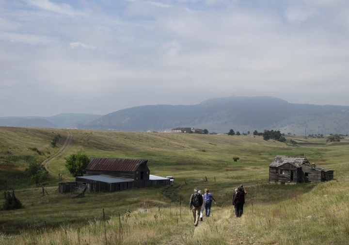FILE--In this Aug. 11, 2017 file photo, visitors approach a former ranch house and barn during a guided hike on the Rocky Flats National Wildlife Refuge near Denver, land that used to be a buffer zone around a nuclear weapons plant. Environmentalists and community activists are trying to stop the refuge from opening to the public this summer, claiming the U.S. Fish and Wildlife Service did not adequately study the safety of the site. (AP Photo/Dan Elliott, File)