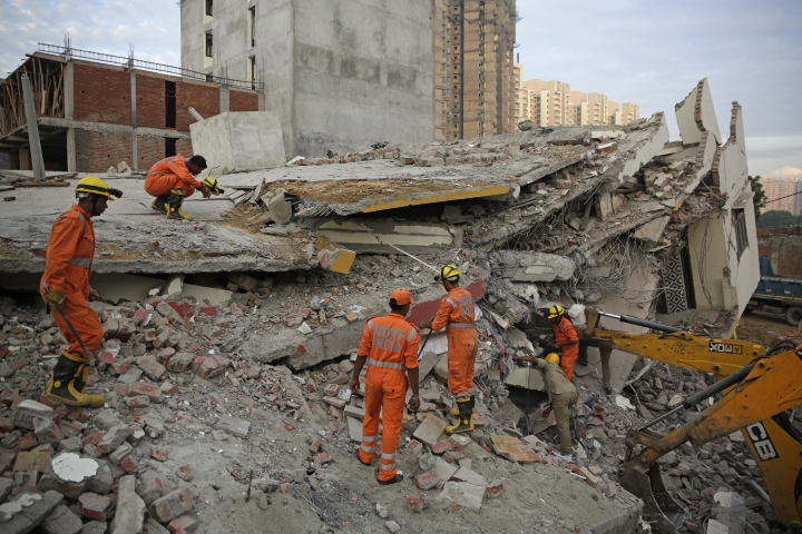 Rescuers search survivors at the site of a building collapsed in Shahberi village, east of New Delhi, India, Wednesday, July 18, 2018. The six-story building under construction collapsed onto an adjacent building. (AP Photo/Altaf Qadri)