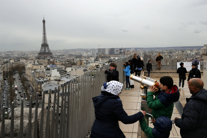 FILE - In this March 21, 2017, file photo, tourists watch Paris from the top of the Arc de Triomphe in Paris, France. The Eiffel Tower is seen background. The American Society of Travel Agents is starting to refer to agents as 'travel advisers' to better describe their emerging roles as trip planners rather than just booking agents. ASTA says they can add value to trips by finding freebies, perks and upgrades along with offbeat and authentic itineraries. (AP Photo/Christophe Ena, File)