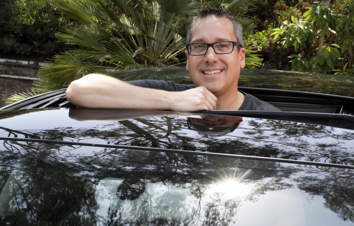 Keith Reynolds, who is on the Tesla waiting list for a Model 3, is photographed by his 9-year-old Audi A3 compact car Monday, July 16, 2018, in Laguna Hills, Calif. For many on the list to buy Tesla's mass-market electric car, the wait for the company to produce enough to satisfy demand isn't a major problem. But the prospect of losing a U.S. federal tax credit is. (AP Photo/Chris Carlson)