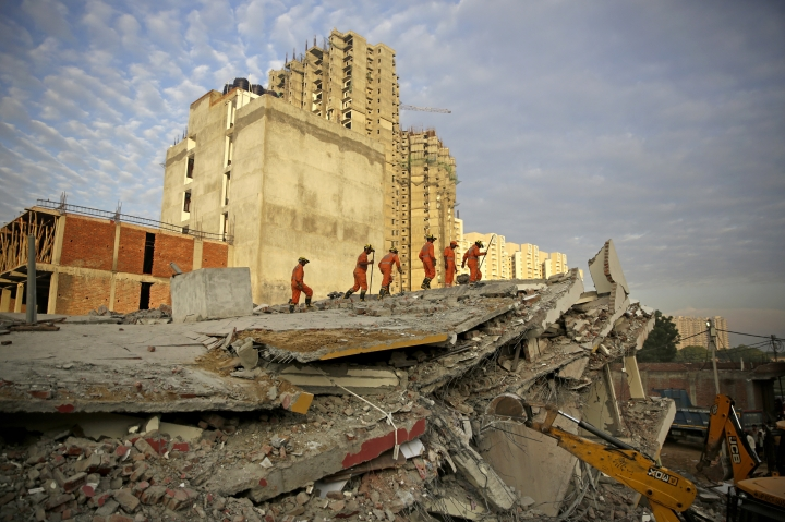 Rescuers work at the site of a collapsed building in Shahberi village, east of New Delhi, India, Wednesday, July 18, 2018. The six-story building under construction collapsed onto an adjacent building. (AP Photo/Altaf Qadri)