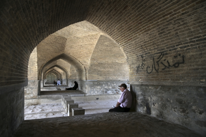 In this Tuesday, July 10, 2018 photo, people rest under an arch of the 400-year-old Si-o-seh Pol bridge, named for its 33 arches, that now spans a dried up Zayandeh Roud river, in Isfahan, Iran. Farmers in central Iran are increasingly turning to protests, pleading to authorities for a solution as years of drought and government mismanagement of water destroy their livelihoods. Their complaints come at a time when protests have repeatedly broken out over economic woes in Iran. (AP Photo/Vahid Salemi)