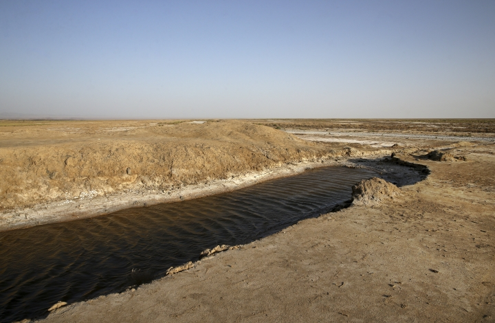 This Tuesday, July 10, 2018 photo, shows one of last puddles of salty water remaining in the the Gavkhouni wetlands, which was once a swamp fed by the Zayandeh Roud river, and is now surrounded by desicated salt-laced fields, outside the town of Varzaneh and its suburbs, home to 30,000 people, some 550 kilometers (340 miles), south of the capital Tehran, Iran. Farmers in central Iran are increasingly turning to protests, pleading to authorities for a solution as years of drought and government mismanagement of water destroy their livelihoods. (AP Photo/Vahid Salemi)