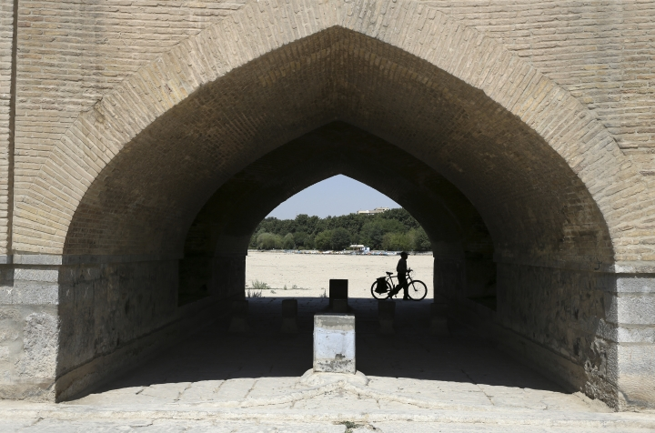 In this Tuesday, July 10, 2018 photo, a man walks his bicycle under the 400-year-old Si-o-seh Pol bridge, named for its 33 arches, that now spans a dried up Zayandeh Roud river, in Isfahan, Iran. Farmers in central Iran are increasingly turning to protests, pleading to authorities for a solution as years of drought and government mismanagement of water destroy their livelihoods. Their complaints come at a time when protests have repeatedly broken out over economic woes in Iran. (AP Photo/Vahid Salemi)