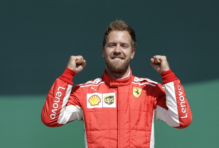 Ferrari driver Sebastian Vettel of Germany celebrates on the podium after winning the British Formula One Grand Prix at the Silverstone racetrack, Silverstone, England, Sunday, July 8, 2018. (AP Photo/Luca Bruno)