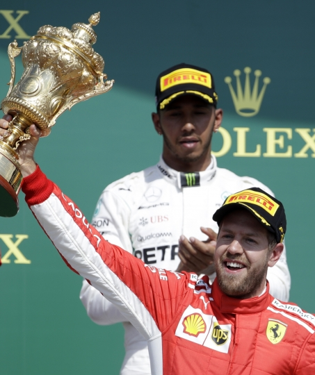 Ferrari driver Sebastian Vettel of Germany, right, celebrates on the podium in front of second placed Mercedes driver Lewis Hamilton of Britain after winning the British Formula One Grand Prix at the Silverstone racetrack, Silverstone, England, Sunday, July 8, 2018. (AP Photo/Luca Bruno)