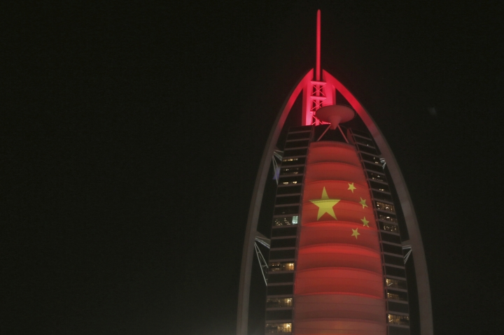 In this Wednesday, July 18, 2018 photo, the Chinese flag is projected onto the Bus Al Arab luxury hotel to celebrate the UAE Chinese Week in Dubai, United Arab Emirates. Chinese President Xi Jinping is heading to Abu Dhabi in his first trip to the United Arab Emirates as the leader of China as the two countries look to strengthen trade ties and expand investment. (AP Photo/Kamran Jebreili)