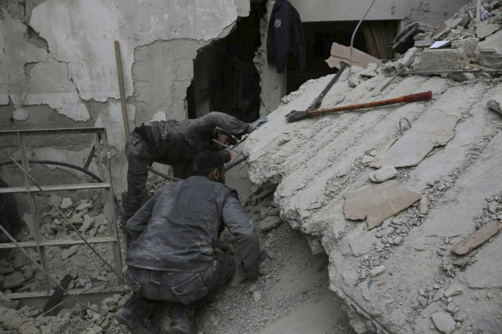 In this photo released on Wednesday Feb. 21, 2018 which provided by the Syrian Civil Defense group known as the White Helmets, shows a member of the Syrian Civil Defense group, searches for victims under the rubble of a destroyed house that attacked by Syrian government forces airstrike, in Ghouta, a suburb of Damascus, Syria. U.S. officials say the United States is finalizing plans to evacuate several hundred Syrian civil defense workers and their families from southwest Syria as Russian-backed government forces close in on the area. U.S., Britain and Canada are spearheading the evacuation that would transport members of the White Helmets group to transit camps in neighboring countries. From there, they will be sent to countries in Europe and possibly Canada. (Syrian Civil Defense White Helmets via AP)