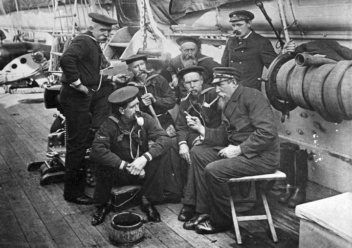 In this circa 1890 photo provided by the Naval History and Heritage Command, seven members of U.S. Navy sit together aboard the USS Enterprise in New York. Though the Navy said in July 2018 that its servicewomen could wear longer hairstyles, servicemen have not been permitted to wear beards, which were banned in 1984. (Naval History and Heritage Command via AP)