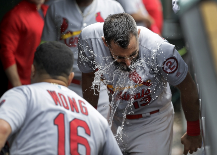 St. Louis Cardinals' Kolten Wong (16) tosses water on Matt Carpenter after Carpenter's third home run of the game, a three-run shot off Chicago Cubs relief pitcher Brian Duensing during the sixth inning of a baseball game Friday, July 20, 2018, in Chicago. Dexter Fowler and Jack Flaherty also scored. (AP Photo/Charles Rex Arbogast)