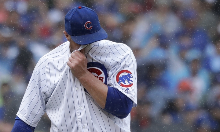 Chicago Cubs starting pitcher Jon Lester wipes the rain from his face after giving up his second home run to St. Louis Cardinals' Matt Carpenter during the second inning of a baseball game Friday, July 20, 2018, in Chicago. Tommy Pham also scored. (AP Photo/Charles Rex Arbogast)