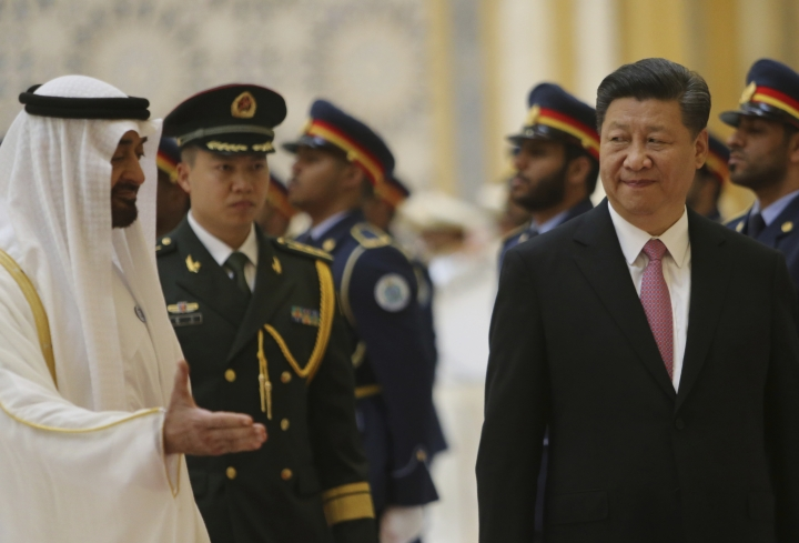 Sheikh Mohamed bin Zayed Al Nahyan, Crown Prince of Abu Dhabi, left, gestures to Chinese President Xi Jinping, right, with Deputy Supreme Commander of the UAE Armed Forces, second left after reviewing the Guard of Honour, at the Presidential Palace in Abu Dhabi, United Arab Emirates, Friday, July 20, 2018. (AP Photo/Malak Harb)